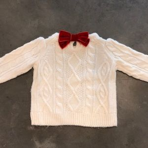White sweater with velvet bow closure on back